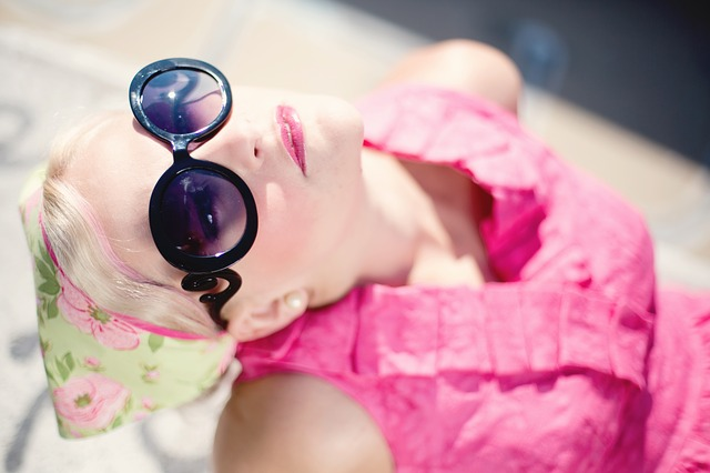 Woman dressed in vintage dress and fifties style sunglasses