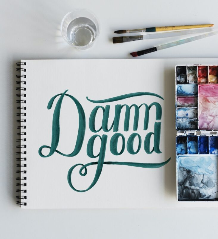 "Watercolor palette with a sketchbook that has painting ""Damn Good"""